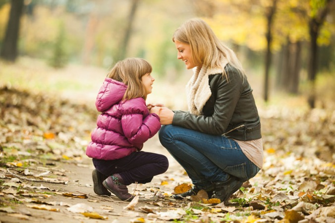 Mother and daughter having fun in park in autumn
